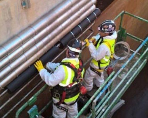 Workers Installing Dragon Jacket Insulation on Pipe Elbow